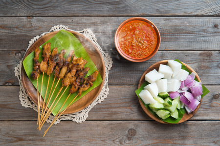 Hot and spicy Asian dish. Chicken sate or satay, skewered and grilled meat, served with peanut sauce. Fresh cooked with steamed and smoke. photo
