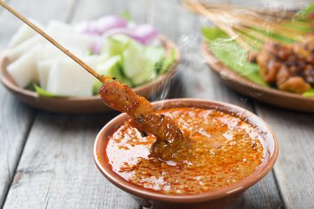 Hete en kruidige Aziatische schotel. Yummy kipsaté of saté, spies en gegrild vlees, geserveerd met pindasaus. Vers bereid met gestoomde en rook. Stockfoto