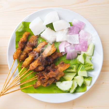 Skewered and grilled meat , chicken sate or satay, served with peanut sauce. Fresh cooked with steamed and smoke. Delicious hot and spicy Asian dish. photo