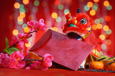 Chinese new year festival decorations, miniature dancing lion and ang pow or red packet with copy space ready for text, on glitter red background. Stock Photo