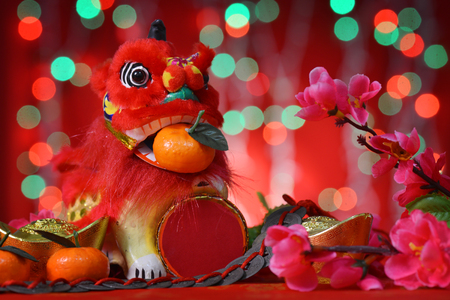 Chinese new year festival decorations, miniature dancing lion and mandarin orange, on glitter red background. photo