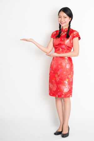 qipao: Portrait of full length Asian Chinese girl, hands showing something, in traditional red cheongsam standing on plain background.