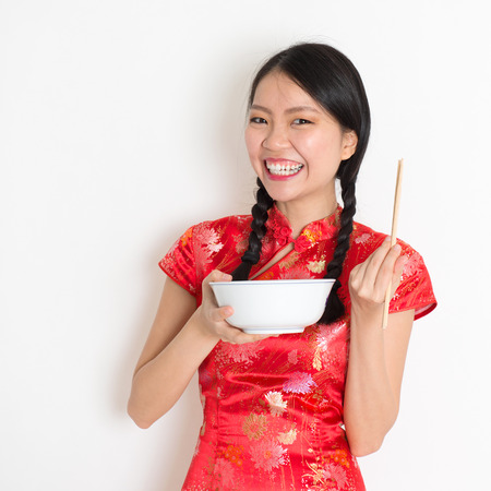 qipao: Portrait of Asian Chinese female eating, using chopsticks holding rice bowl, in traditional dress red cheongsam standing on plain background. Stock Photo