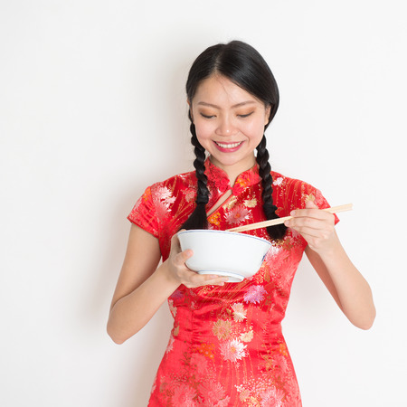 qipao: Portrait of Asian Chinese female eating, using chopsticks holding rice bowl, in traditional dress red qipao standing on plain background. Stock Photo