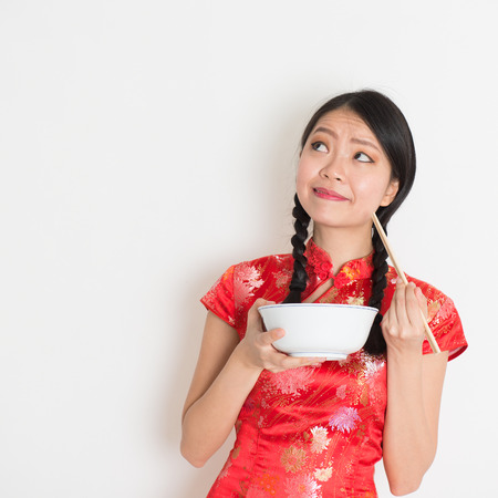 chinese new year food: Asian Chinese female eating using chopsticks holding rice bowl, in traditional cheongsam on plain background, thinking and looking up at copy space.