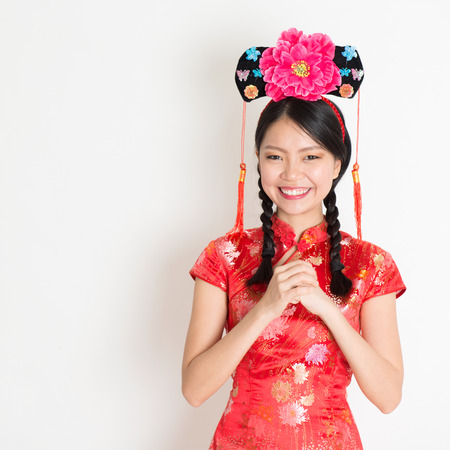 qipao: Portrait of Asian Chinese girl with princess hat greeting, in traditional red qipao standing on plain background.