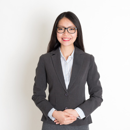 pan asian: Asian business woman smiling at camera, standing on plain background. Stock Photo
