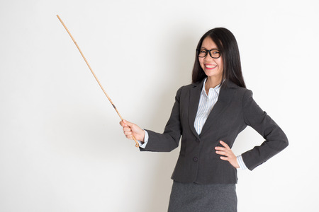 asian teacher: Asian female teacher smiling and holding a stick, standing on plain background.