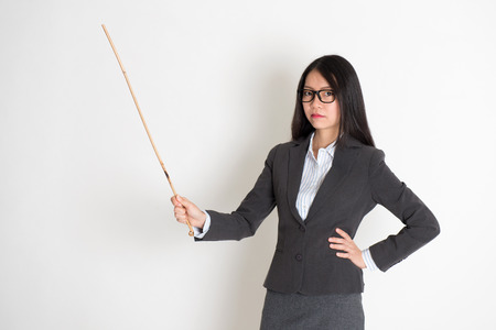 Asian female teacher angry and holding a stick, standing on plain background. Stock Photo