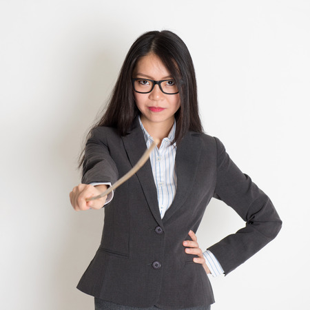Asian female teacher holding a stick pointing at camera, standing on plain background.