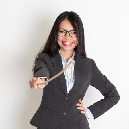 asian teacher: Asian female teacher smiling and holding a stick pointing at camera, standing on plain background.
