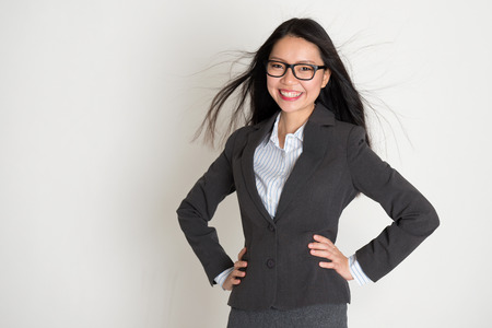 pan asian: Beautiful young Asian business woman smiling at camera, standing on plain background.