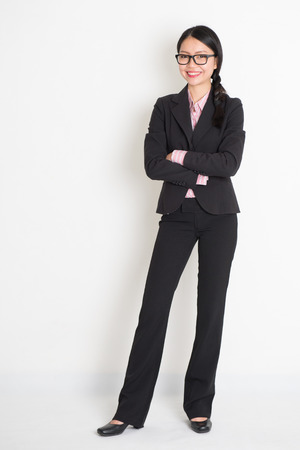 the whole body: Full body Asian business woman smiling and standing on plain background.
