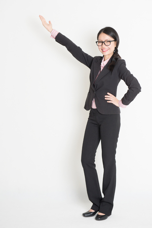 Full body Asian business woman showing copy space, standing on plain background. photo