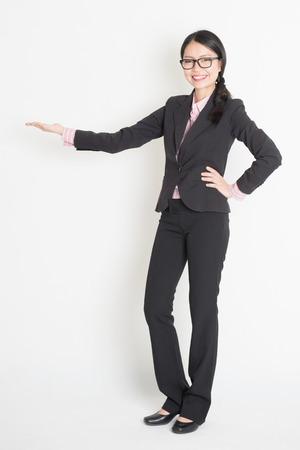 alzando la mano: Todo el cuerpo de la mujer de negocios de Asia mostrando copia espacio, de la mano algo, de pie en el fondo plano.