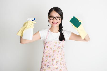 Asia mujer ama de casa joven chino, rociando detergente y húmeda sobre vidrio sucio.
