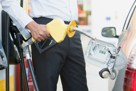 pumping: Close up Asian man pumping gasoline fuel in car at gas station. Stock Photo