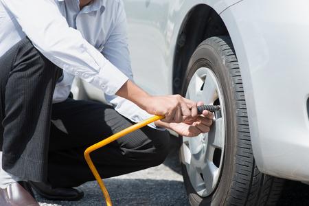 Aziatische bestuurder controleren van de luchtdruk en het vullen van de lucht in de banden van zijn auto. Stockfoto