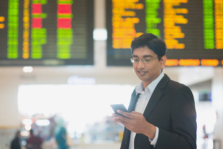 Asian Indian Business man checking on smartphone, doing online web check in at the airport . Stock Photo