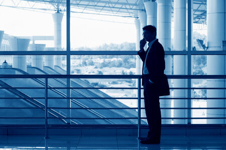 businessman waiting call: Silhouette of Asian Indian man on mobile phone in modern office building, blue tone. Stock Photo