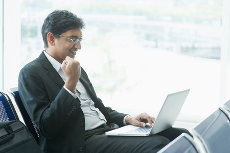 business traveller: Asian Indian businessman sitting on chair and using laptop while waiting his flight at airport.