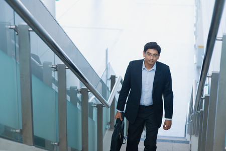 malaysia city: Asian Indian corporate businessman in suit with briefcase ascending steps.