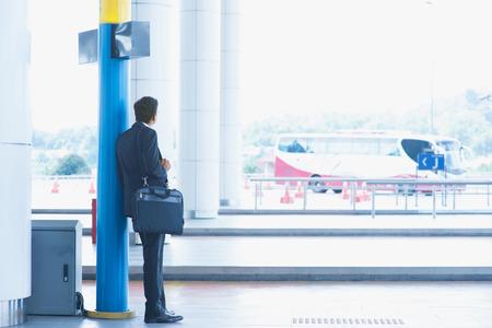 Achteraanzicht full body Aziatische Indiase zakenman wachten bus bij openbare busstation.