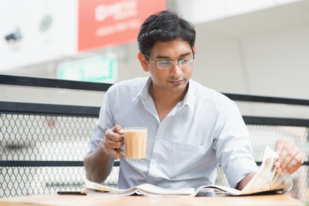 lunch hour: Asian Indian businessman reading newspaper while drinking a cup hot milk tea during lunch hour at cafeteria.