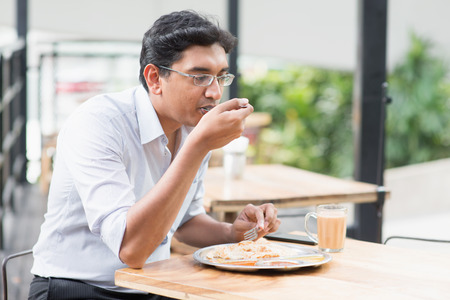 business dinner: Asian Indian business man eating food at cafeteria. Stock Photo