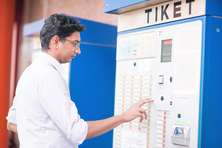 ticketing: Asian Indian businessman buying transport ticket at vending machine.