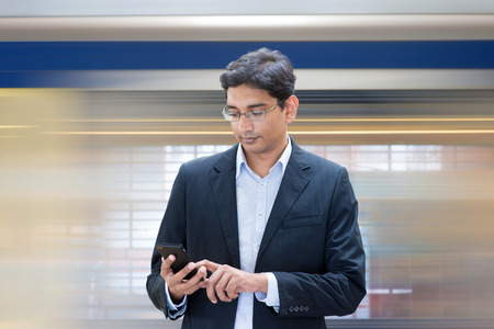 Asian Indian businessman texting using smartphone while waiting train at railway station. photo