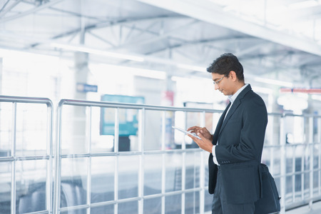 Asian Indian businessman using tablet computer while waiting train at railway station.