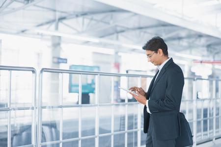 tableta: Asijský indický podnikatel pomocí počítače tablet při čekání vlaku na nádraží.