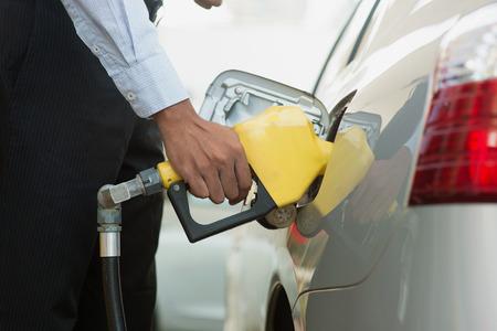 fuelling station: El bombeo de gas. Close up de hombre de bombeo de combustible de gasolina en el coche en la gasolinera.