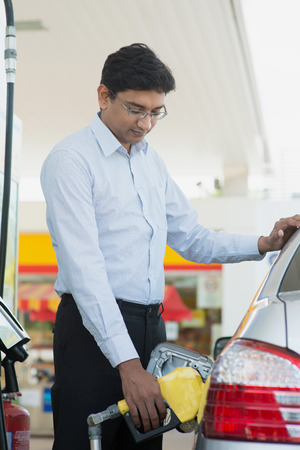 Pumping gas. Asian Indian man pumping gasoline fuel in car at gas station. Stock Photo