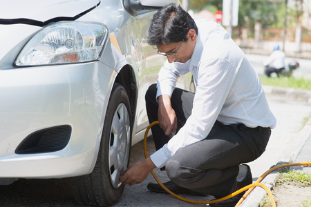 Indian driver checking air pressure and filling air in the tires of his car.