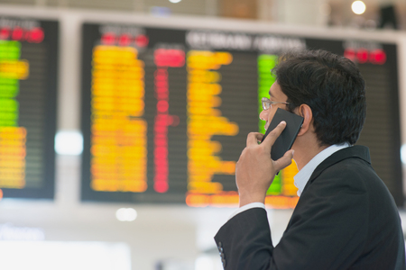 Asian Businessman looking at airport flight timetable and on the phone. photo