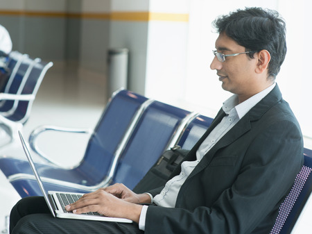 wireless terminals: Asian Indian business man sitting on chair and using laptop while waiting his flight at airport.