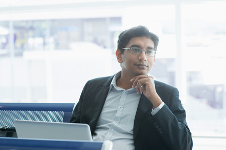 thinking: Asian Indian business man waiting his flight at airport.