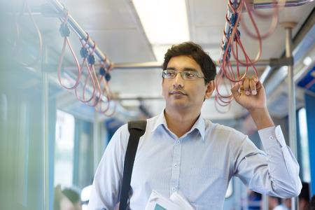 アジアのインド ビジネス男撮影に乗って作業、電車の中に立っています。 写真素材