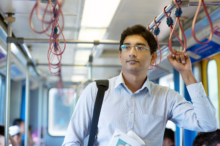 Asian Indian businessman taking ride to work, standing inside train. Stock Photo