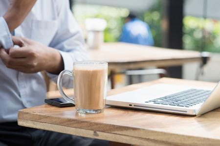 office break: Hombre de negocios indio asi�tico que tiene un t� con leche caliente taza y laminado en la manga durante las vacaciones de la oficina.