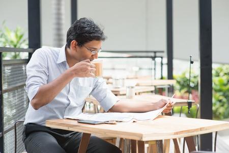 almuerzo: Asia hombre de negocios indio leyendo el peri�dico mientras bebe una taza de t� de leche caliente durante la hora del almuerzo en la cafeter�a.