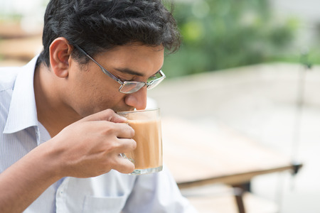 lunch hour: Asian Indian businessman sipping a cup hot milk tea during lunch hour at cafeteria.