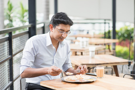 Asian Indian businessman eating food at cafeteria.