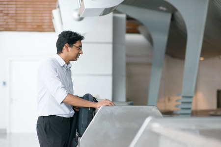 airport check in counter: Asian Indian businessman standing by airport check in counter