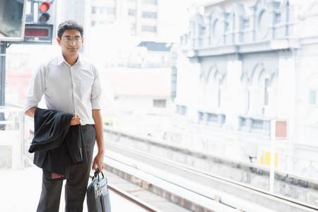 indian people: Asian Indian business people waiting train at railway station. Stock Photo