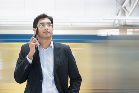 businessman waiting call: Asian Indian businessman on the phone while waiting train at railway station.