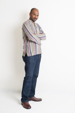 Full body Asian Indian guy in casual wear crossed arms standing on plain background with shadow. Stock Photo