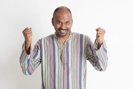 pakistani ethnicity: Portrait of happy Asian Indian man celebrating success over plain background